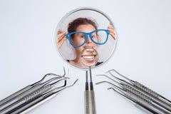 Las herramientas del dentista y los dos espejos del dentista con la sonrisa de la mujer fotografía de archivo