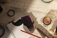 Las herramientas del padre, bigote de papel negro, lupa, lápices en una tabla de madera ligera imagenes de archivo