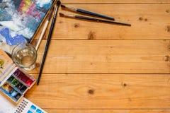 Las herramientas del ` s del artista en una tabla de madera imagen de archivo
