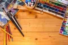 Las herramientas del ` s del artista en una tabla de madera foto de archivo libre de regalías