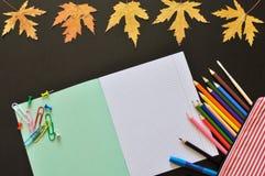 Las herramientas educativas tales como cuaderno, pluma dibujaron a lápiz, etc en un fondo oscuro con las hojas de otoño Copyspace foto de archivo libre de regalías