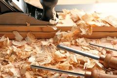 Las herramientas, los tableros y la sierra del ` s del carpintero sacan el polvo en la tabla de madera foto de archivo libre de regalías