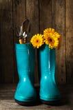 Las herramientas que cultivan un huerto con las botas de goma azules, amarillean las flores de la primavera encendido Fotografía de archivo libre de regalías
