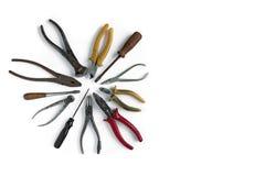 Las herramientas viejas mienten en un fondo aislado blanco Cinceles, cortaalambres, destornillador, alicates y otras herramientas foto de archivo