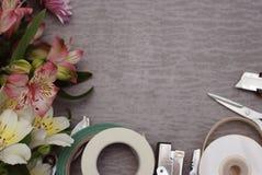 Las herramientas y los floristas de los accesorios necesitan para componer un ramo en la superficie de madera gris, concepto, lug imagen de archivo