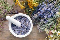 Las hierbas y el mortero medicinales llenaron de las flores de la lavanda Foto de archivo libre de regalías