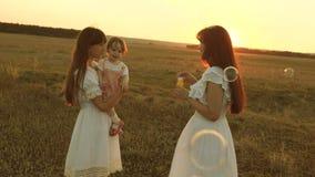 Las hijas disfrutan y sonr?en, las burbujas vuelan en parque en la puesta del sol C?mara lenta Madre feliz que juega con los ni?o almacen de video