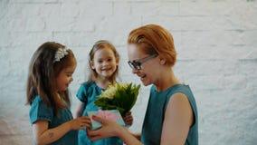 Las hijas preciosas dan a mamá un regalo y las flores