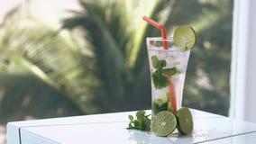 Las hojas de palma verdes se mueven en brisa detrás de la tabla con la bebida metrajes