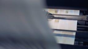 Las hojas de papel impresas sin cortar están siendo procesadas el equipo industrial y moviéndose a lo largo de ella en una direcc almacen de video
