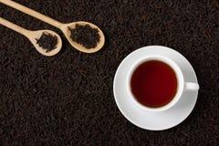 Las hojas de té negras secas texturizan la taza de madera de las cucharas del fondo fotos de archivo libres de regalías