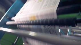 Las hojas del periódico suben en una planta de fabricación, cierre almacen de metraje de vídeo