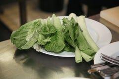 Las hojas lavadas son ensalada verde fresca en una placa blanca Imagen de archivo