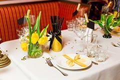 Las huéspedes del cumpleaños presentan el ajuste con las flores frescas en el negro y el estilo del oro, interiores Foto de archivo libre de regalías