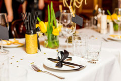 Las huéspedes del cumpleaños presentan el ajuste con las flores frescas en el negro y el estilo del oro, interiores Imagen de archivo libre de regalías