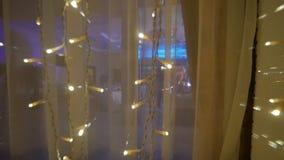 Las huéspedes en el festival están bailando y se están divirtiendo, la visión desde la ventana, luces de la Navidad, cámara lenta metrajes