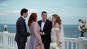 Las huéspedes en la boda felicitan la novia y al novio en la ceremonia que se casa Un par joven en soportes del amor en almacen de metraje de vídeo