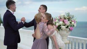 Las huéspedes en la boda felicitan la novia y al novio en la ceremonia que se casa Un par joven en soportes del amor en metrajes