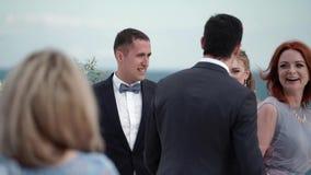 Las huéspedes en la boda felicitan la novia y al novio en la ceremonia que se casa Un par joven en soportes del amor en almacen de video