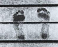 Las huellas descalzas se cierran para arriba en el embarcadero de madera con nieve blanca clara en invierno Imagenes de archivo