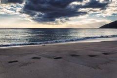 Las huellas en la arena y la opinión del mar de la tarde en Makua varan, Oahu imagen de archivo