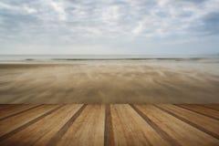 Las huellas en puesta del sol del verano de la playa ajardinan con los tablones de madera f Foto de archivo libre de regalías