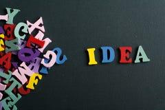 Las IDEAS redactan en el fondo negro del tablero compuesto de letras de madera del ABC del bloque colorido del alfabeto, copian e Foto de archivo