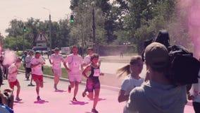 Las imágenes de la toma del cameraman y del fotógrafo, mientras que los organizadores lanzan, lanzan el holi, rosa, pintura color metrajes