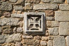 Las insignias de la orden de la cruz de Cristo de la orden de Cristo adentro como pared de piedra vieja en el pueblo histórico de Foto de archivo libre de regalías