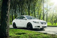 Las insignias de Opel del coche se colocan en la carretera de asfalto en bosque verde en el d3ia Imagen de archivo libre de regalías