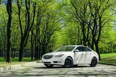 Las insignias de Opel del coche se colocan en la carretera de asfalto en bosque verde en el d3ia Fotos de archivo libres de regalías