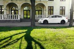 Las insignias de Opel del coche se colocan en la carretera de asfalto en bosque verde en el d3ia Fotografía de archivo