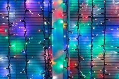 Las lámparas multicoloras de la Navidad adornan la ventana Fotografía de archivo libre de regalías