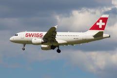 Las líneas aéreas internacionales suizas de Airbus A319-112 HB-IPY en el fondo del cielo nublado Imagen de archivo libre de regalías