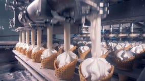 Las líneas de conos de la galleta están consiguiendo llenaron de la sustancia del helado almacen de video