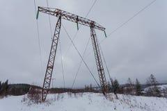 Las líneas eléctricas de la transmisión de la electricidad en alto voltaje del fondo del invierno se elevan Foto de archivo libre de regalías
