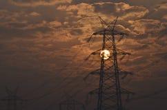 Las líneas eléctricas eléctricas del pilón y del alto voltaje acercan a la estación de la transformación en la salida del sol en  Imagen de archivo