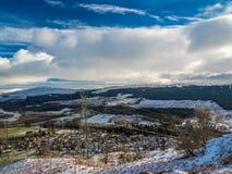 Las líneas eléctricas y los pilones de arriba marcan con una cicatriz las montañas escocesas fotografía de archivo