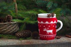 Las lanas hechas a mano de la Navidad hechas punto envolvieron la taza con el fondo rústico del canela de los pinos de los conos  Imagenes de archivo