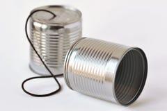 Las latas llaman por teléfono en el fondo blanco - concepto de la comunicación foto de archivo
