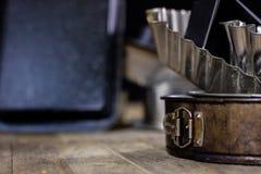 Las latas y la hornada forma en una tabla de madera Accesorios viejos de la cocina Foto de archivo libre de regalías