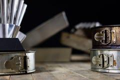Las latas y la hornada forma en una tabla de madera Accesorios viejos de la cocina Imagen de archivo