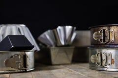 Las latas y la hornada forma en una tabla de madera Accesorios viejos de la cocina Fotografía de archivo