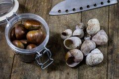 Las latas y la hornada forma en una tabla de madera Accesorios viejos de la cocina en la tabla de cocina Fotografía de archivo