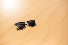 Las lentes de sol negros el verano abandonan las dunas de arena en la arena Foto de archivo