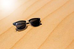 Las lentes de sol negros el verano abandonan las dunas de arena en la arena Fotografía de archivo