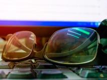 Las lentes en el teclado negro con el monitor, relajan el concep del tiempo Foto de archivo