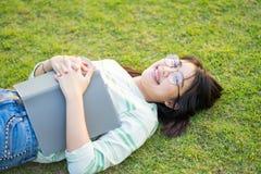 Las lentes que llevan del adolescente asiático mienten en prado con un libro en la puesta del sol Imagen de archivo