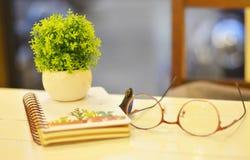 Las lentes reservan y los pequeños potes en una tabla de madera blanca Imagen de archivo