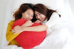 Las lesbianas lindas jovenes de Asia que llevan a cabo el corazón rojo forman el sauce juntas Fotografía de archivo libre de regalías